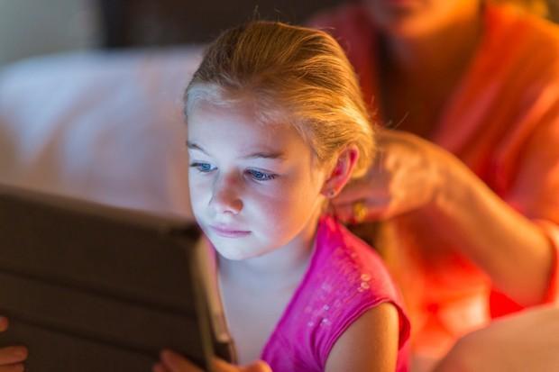 Caucasian girl using digital tablet as mother braids hair