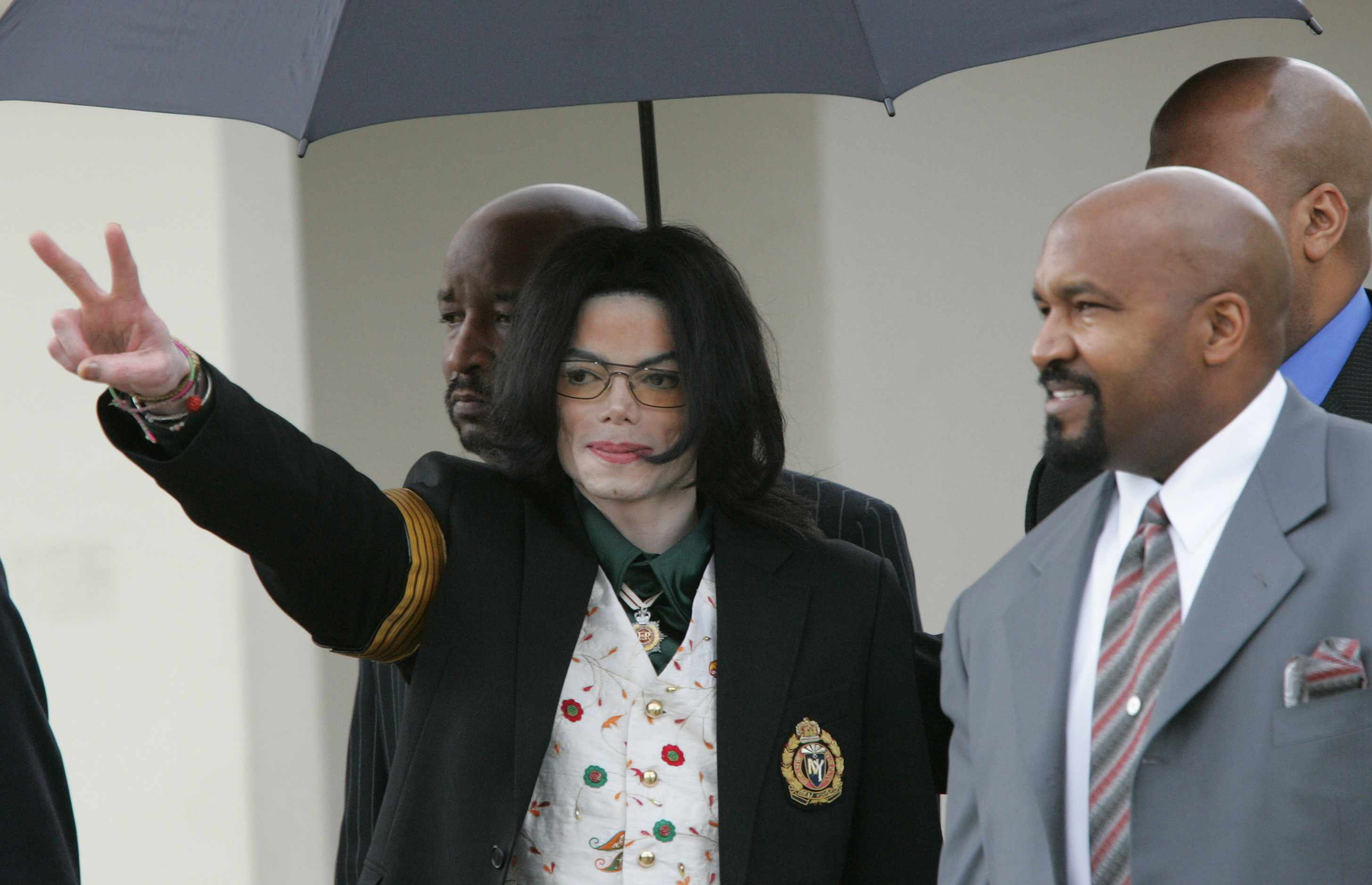 Pop singer Michael Jackson gestures as he leaves the Santa Barbara County Courts with his bodyguards for the third day of his child molestation trial. The entertainer faces ten counts of felony molestation of a male minor at his Neverland Ranch. (Photo by Kimberly White/Corbis via Getty Images)