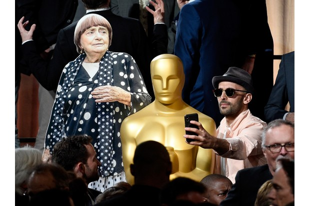 Varda's collaborator and filmmaker JR takes a selfie with an Oscar statue and a cardboard cutout of Agnes Varda during the Oscar nominees