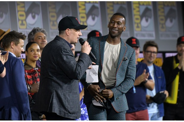 President of Marvel studios Kevin Feige (C) welcomes US actor Mahershala Ali on stage during the Marvel panel in Hall H of the Convention Center during Comic Con in San Diego, California on July 20, 2019. (Photo by Chris Delmas / AFP) (Photo credit should read CHRIS DELMAS/AFP/Getty Images)