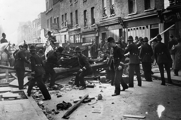 Police take down a barricade during the Battle of Cable Street