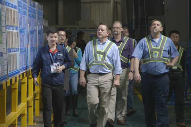 American Fuyao management team members Marvin Disney (center), Rodney Brickey (purple shirt), Jon Helton (right) and others tour a Fuyao factory in Fuqing, Fujian Province China - from the film AMERICAN FACTORY