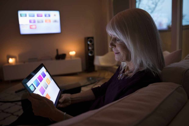 Senior woman using smart TV apps on digital tablet on living room sofa