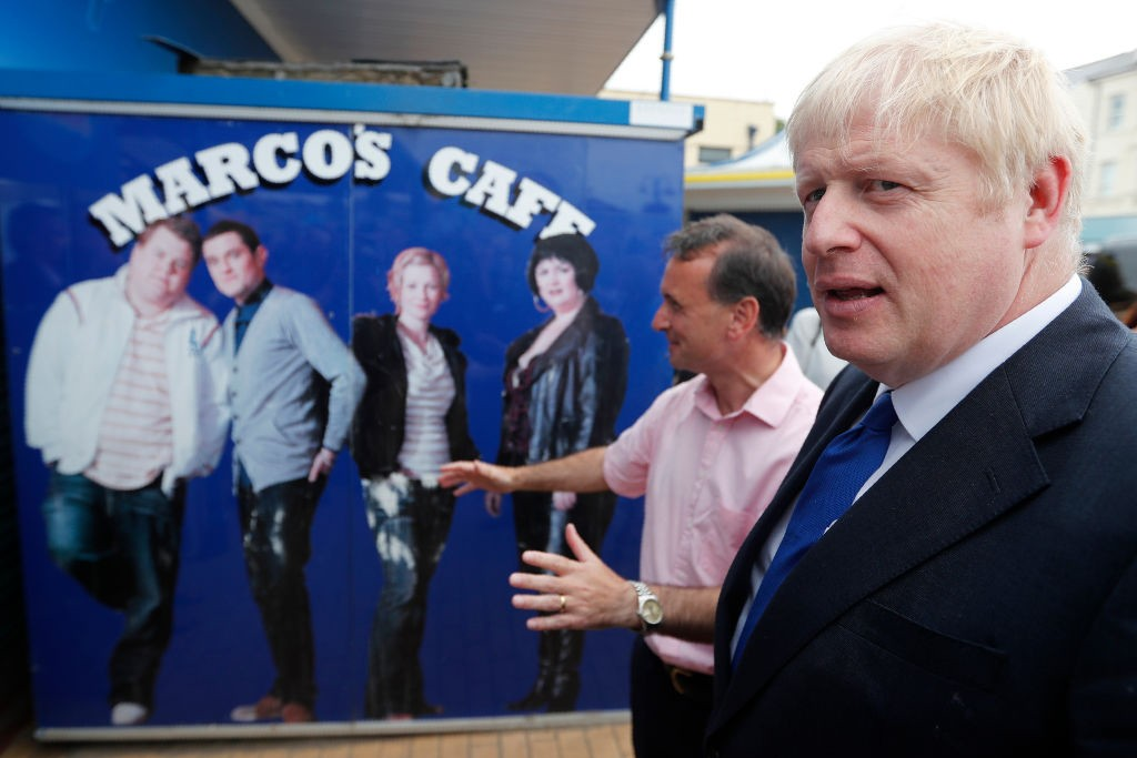 Boris Johnson and Alun Cairns, Secretary of State in Wales, pose for photos in front of the cafe featured in the comedy series Gavin and Stacey, as he visits Barry Island ahead of the Conservative party leadership hustings in Cardiff, on July 06, 2019 in Barry, Wales (Getty)