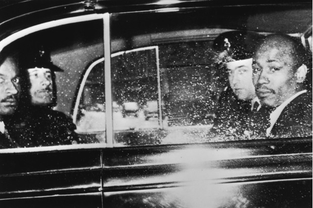 Aloysius 'Lucky' Gordon and Johnny Edgecombe, witnesses in the Profumo Affair, leave the Treasury by car with a police escort, 10th July 1963. Both men had been involved with showgirl Christine Keeler. (Photo by Keystone/Hulton Archive/Getty Images)