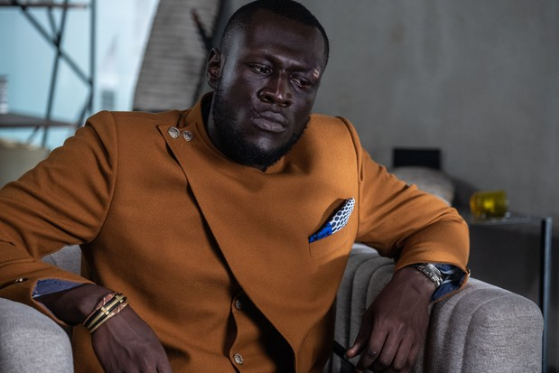 """WARNING: Embargoed for publication until 00:00:01 on 25/02/2020 - Programme Name: Noughts & Crosses - TX: 05/03/2020 - Episode: n/a (No. n/a) - Picture Shows: British musician Stormzy has joined the cast of the much anticipated BBC One drama Noughts + Crosses, a Mammoth Screen adaptation of Malorie Blackman's award-winning young adult book series currently being filmed in South Africa. Stormzy will play newspaper editor Kolawale, a character created for the TV series, and admits: """"As a diehard fan of Malorie's novels, being a part of this important show is a dream come true."""" Malorie Blackman says: """"The first time I met Stormzy he informed me he was a huge fan of my Noughts and Crosses series of books.  I'm thrilled he will now be a part of the Noughts + Crosses TV production.  It's so exciting!"""" Executive producer Preethi Mavahalli, Mammoth Screen adds: """"As an icon of black British culture, we are honoured to have Stormzy play a part in this adaptation of a novel he's such a fan of.""""   A gripping story of first love in a dangerous, alternate world where racism divides society BAFTA Cymru winner Jack Rowan (Peaky Blinders, Born to Kill) will play Callum McGregor and newcomer Masali Baduza has been cast as Sephy Hadley. Other cast include Helen Baxendale, Paterson Joseph and Ian Hart. Noughts + Crosses will air on BBC One. Kolawale (STORMZY) - (C) Mammoth Screen - Photographer: Ilze Kitshoff"""