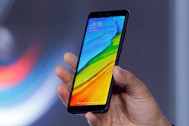 """PARIS, FRANCE - MAY 22:  Senior Vice President, Wang Xian of the Chinese electronics and computer company Xiaomi specializing in mobile telephony Xiaomi shows a  Redmi Note 5 smartphone at the Intercontinental Paris Grand Hotel during the presentation of the first Xiaomi store on May 22, 2018 in Paris, France. Xiaomi officially opened its first store in France, """"boulevard de Sebastopol"""" in Paris. Xiaomi or Mi is now in 5th place in the world ranking of smartphone brands.  (Photo by Chesnot/Getty Images)"""