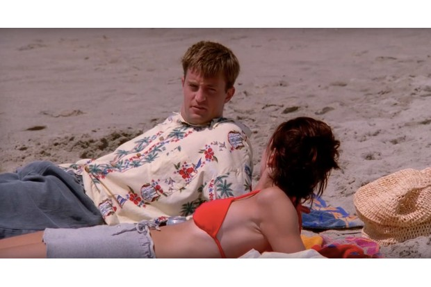 Chandler and Monica from Friends lying on the beach