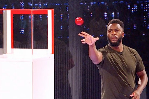 Mo Gilligan trying to bounce a ball into a box on The Million Pound Cube Celebrity