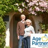 Senior Couple Standing Outside Pretty Cottage