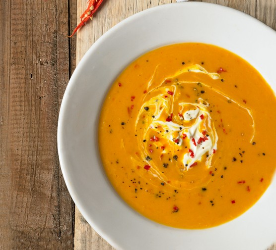 Butternut squash and chilli soup in a bowl, with a swirl of cream