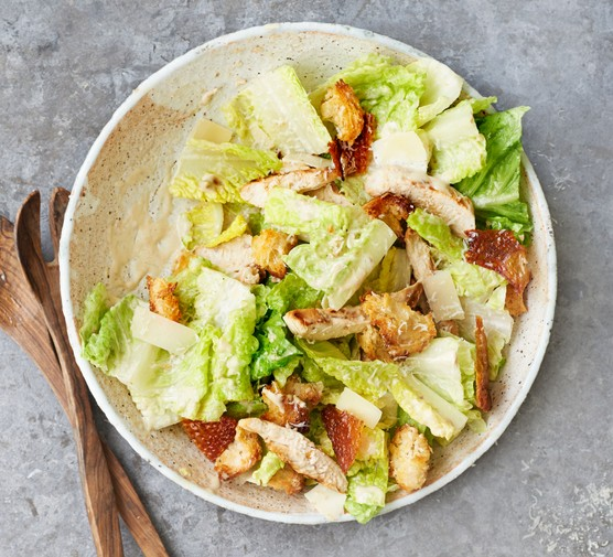 Bowl of chicken Caesar salad with croutons and cutlery