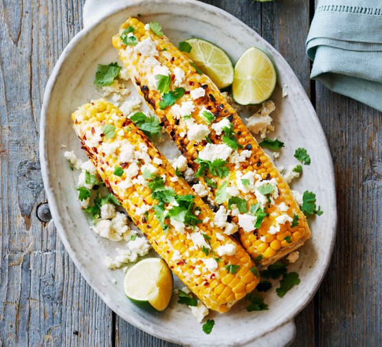 Two charred corn on the cobs topped with herbs and feta