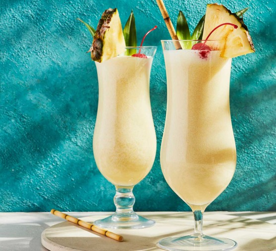 Pina colada cocktails in glasses with pineapple wedges