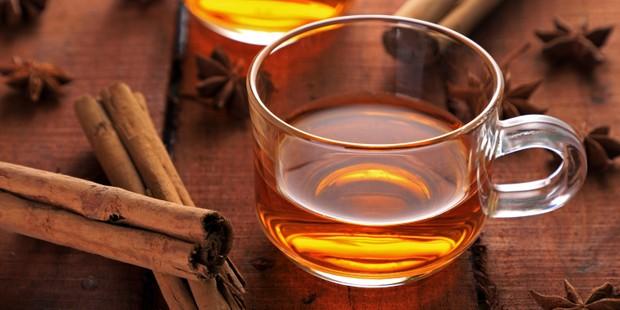 Cinnamon tea in a glass with cinnamon sticks