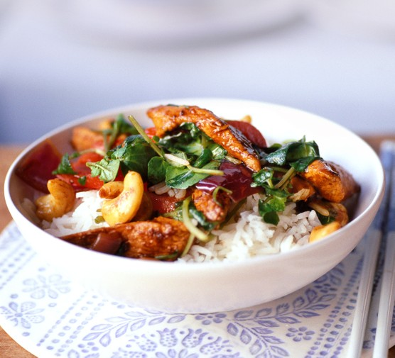Watercress and chicken noodles in a bowl with rice