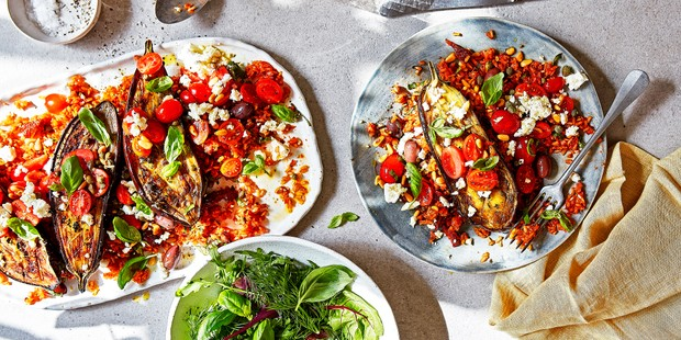 Aubergine puttanesca on two plates, served with salad