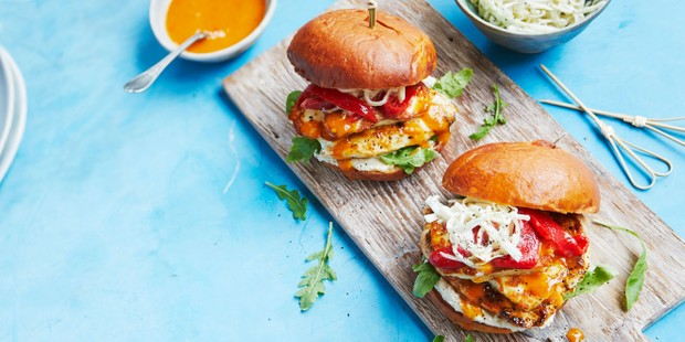 Halloumi and chicken burgers on a board, with dipping sauce