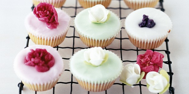 Pink and green fairy cakes topped with icing and roses