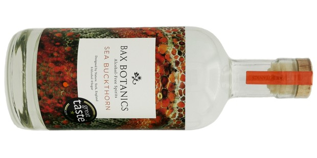 A bottle of Bax botanics Sea Buckthorn 0n its side against a white background