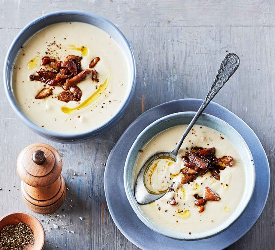 Two bowls of Jerusalem artichoke soup topped with bacon lardons