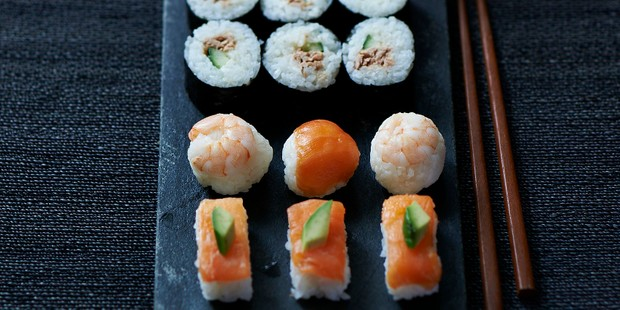 различные суши и сашими на грифельной тарелке