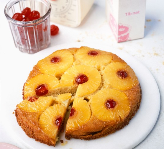 Pineapple upside down cake with a jar of cherries in the background