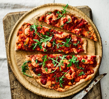Prawn-topped pizza with rocket leaves, sliced on a wooden board