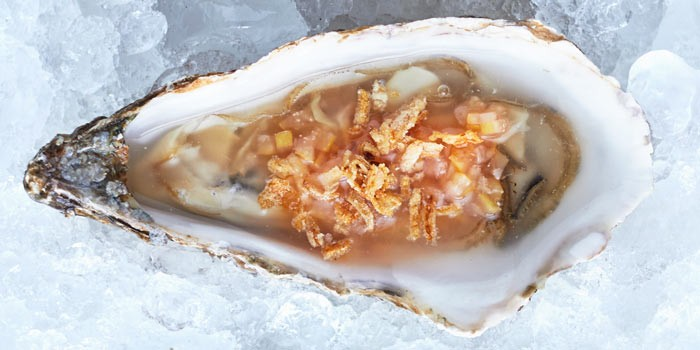 Oyster with preserved lemon peel on ice