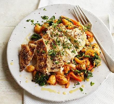 Chicken with crushed harissa chickpeas served on a plate