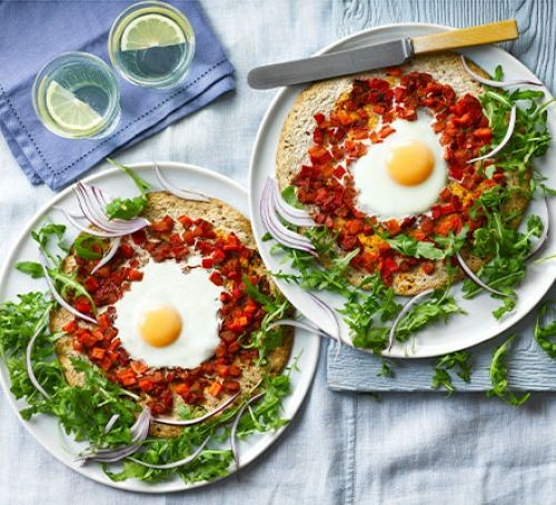 Two tortilla pizzas topped with eggs, tomato and rocket leaves