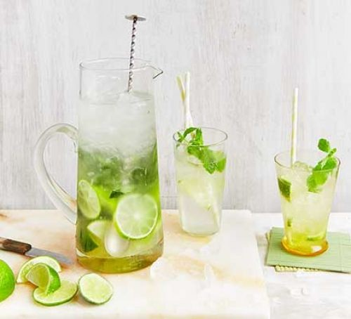 Pitcher and glasses of mojito filled with lime and mint