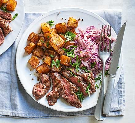 Smoky steak with Cajun potatoes & spicy slaw served on a plate