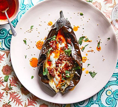 Roasted aubergine on white plate with harissa