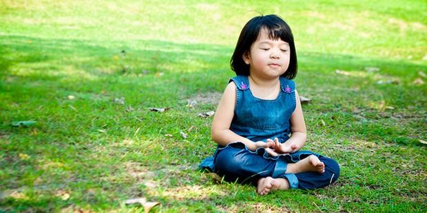 Toddler meditating outside