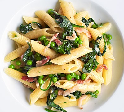 Pasta with spinach in white bowl