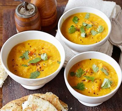 Three white bowls of butternut squash soup