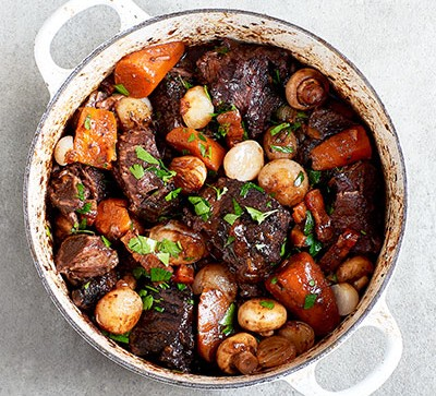 Beef bourguignon in white pot on grey backdrop