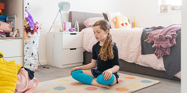 Child meditating in bedroom
