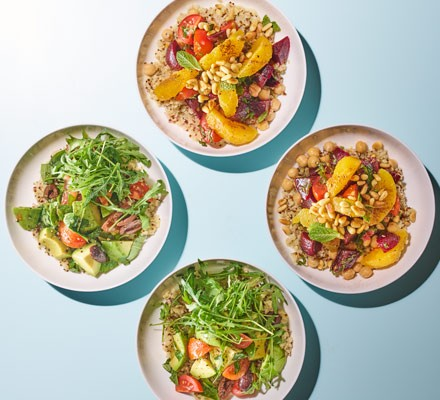 Four bowls with a grain mix of bulgur and quinoa with various toppings