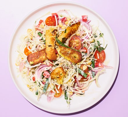A plate of coleslaw-style salad topped with cumin-spiced halloumi