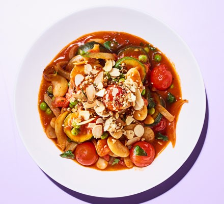 A bowl of courgette stew served with a spicy sesame seed and flaked almond topping