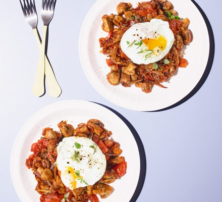 Two plates of mushroom potato hash with poached eggs on top