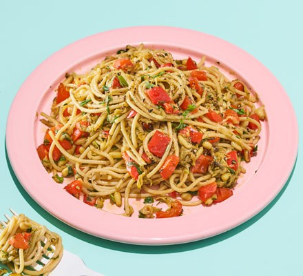 A plate of spaghetti served with red pepper, lemon, basil and pine nuts