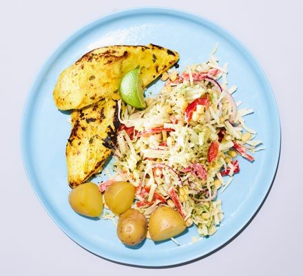 A plate of chicken with coleslaw and potatoes