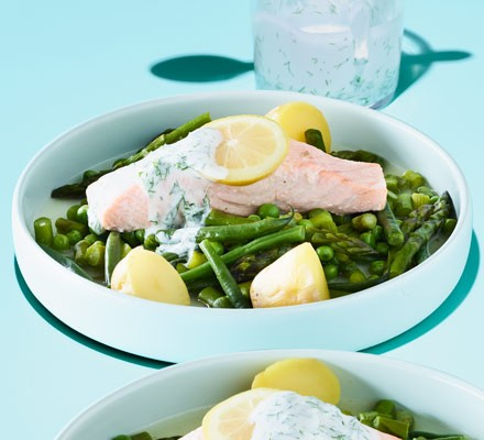 A bowl with potatoes, asparagus, beans, peas and trout fillets with a dill sauce