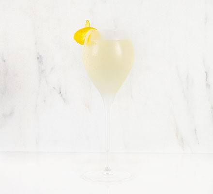 A French 75 cocktail served with a strip of lemon zest
