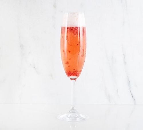 Raspberry champagne cocktail in glass