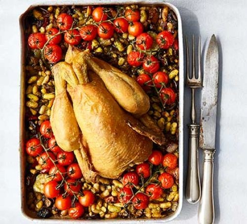 Roast chicken in tray with tomatoes