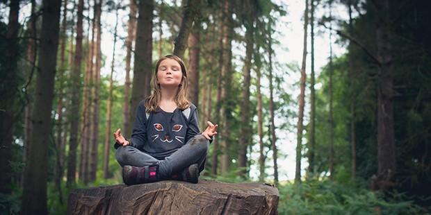 Girl meditating in woodland